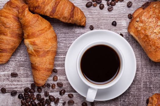 Cup of hot coffee and freshly baked croissants on dark wooden table. Tasty croissant.
