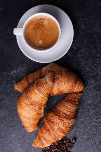 Top view of traditional croissants with hot coffee. Golden croissants.