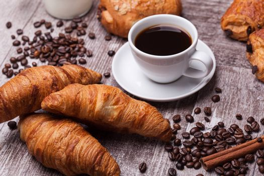 Coffee and croissant for breakfast on rustic wooden table. Tasty food.