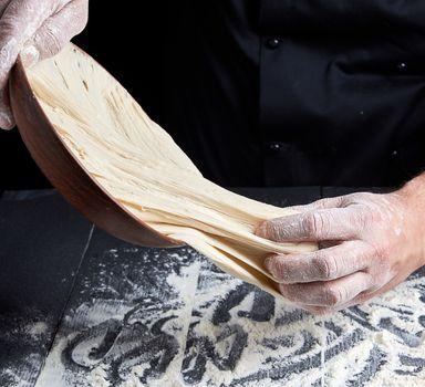 man's hands knead white wheat flour dough