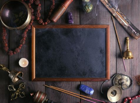 Tibetan singing bowl and other religious ritual instruments for meditation and empty frame on a brown wooden background, top view,