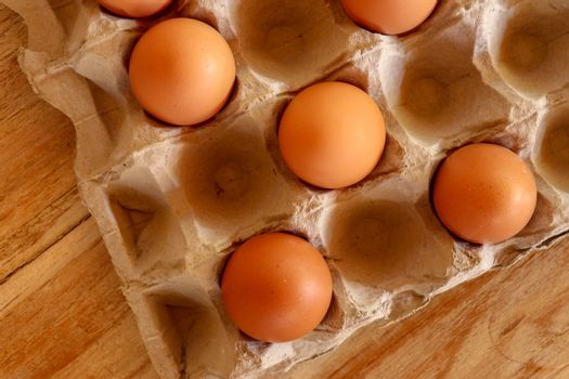 Thirty brown chicken eggs in a cardboard tray packaging. Raw fresh hen eggs in a carton box. Egg pattern background for easter, breakfast, cuisine. Top view