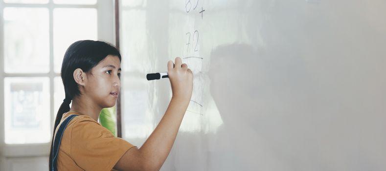 School child thinking while doing mathematics problem. Education concept.