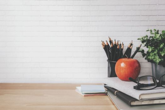 Copyspace of minimal workplace with office supplies on wooden table and white wall background.