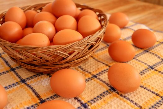 Brown chicken egg on vintage tablecloth and eggs in the basket.