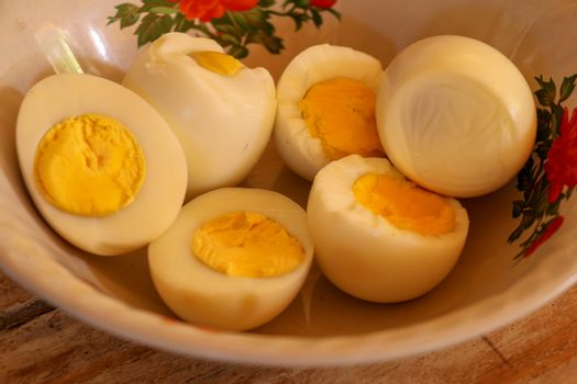 close up of half boiled eggs on wooden bowl.