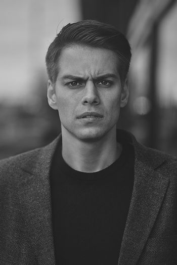 Portrait of manly stunning man in coat looking at camera standing on street.