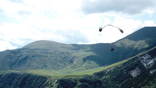 Paraglider flying over mountains during summer day - Georgia