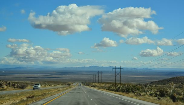 Straight road in a valley of mountains in New Mexico