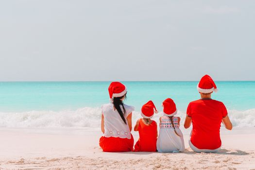 Happy family in Xmas hats on tropical beach on Christmas vacation