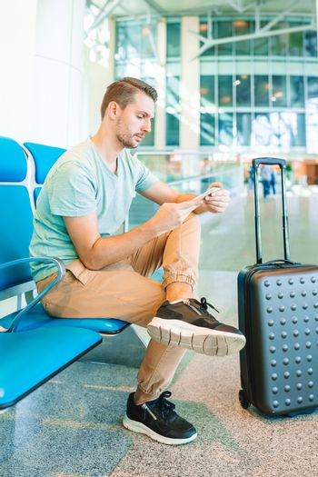 Airline passenger in an airport lounge waiting for flight aircraft.