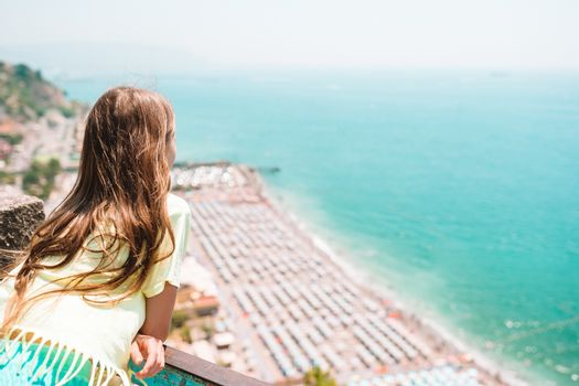 Young girl in background of mediterranean sea and sky.
