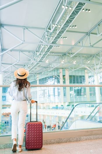 Young woman in hat with baggage in international airport.