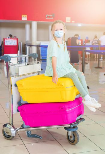 Little adorable kid with surgical mask face protection at international airport.