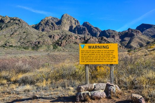 """""""WARNING"""" sign against mountain landscape with cacti, New Mexico"""