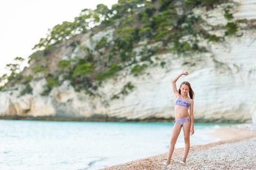 Adorable little girl on the seashore alone