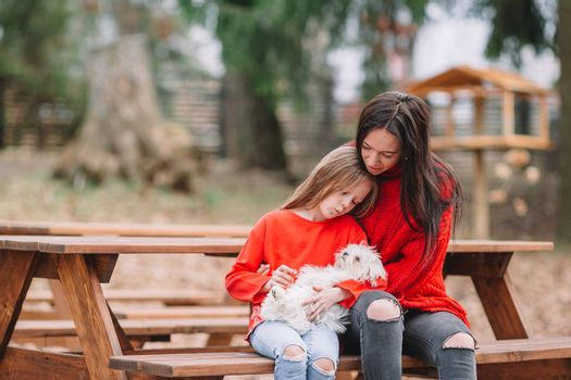 Adorable little kid and young mother with puppy outdoor
