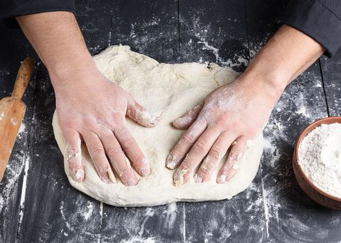 men's hands knead a round piece of dough for making pizza
