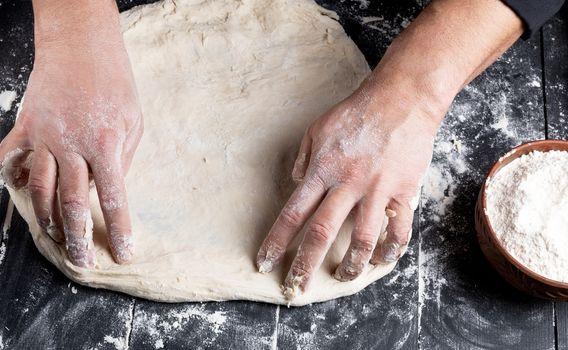 men's hands knead a round piece of dough