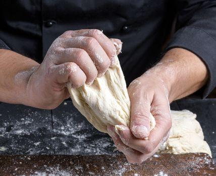 men's hands knead white wheat flour dough