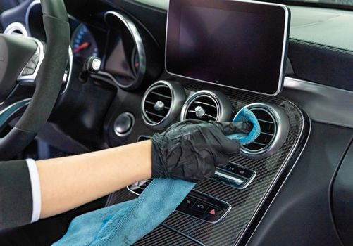 manual cleaning of the interior of luxury cars with a microfiber cloth