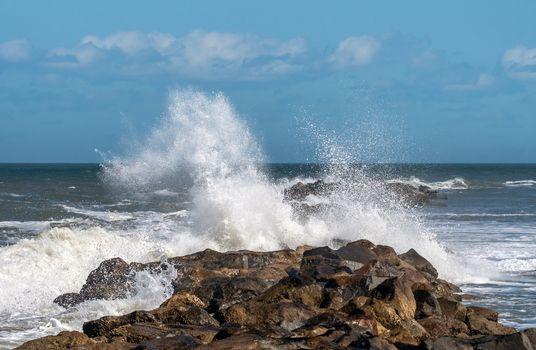 Crashing waves break over a jetty wall