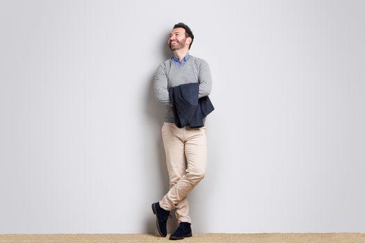 Full body happy businessman against gray wall