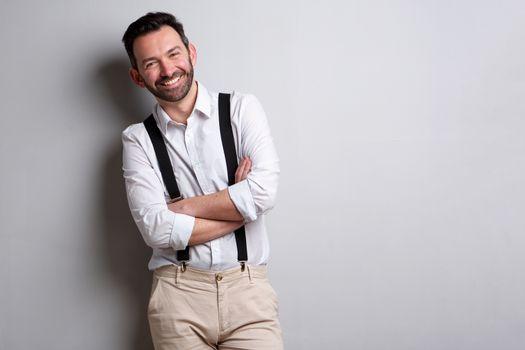 happy man with beard posing against gray wall