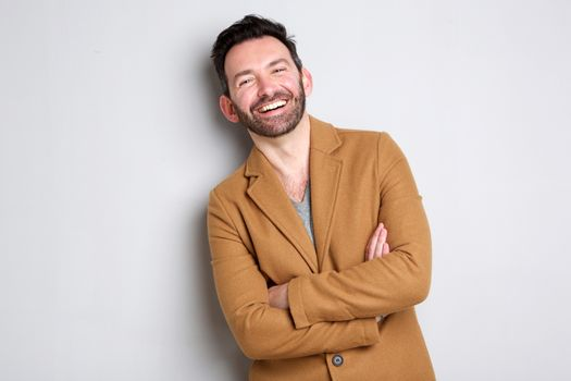 happy man with beard smiling against gray wall