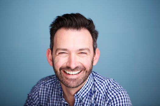 Close up smiling man with beard against blue background