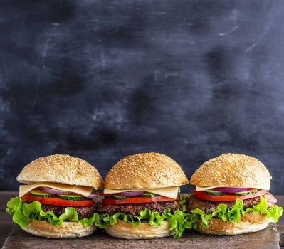 three hamburgers with vegetables on a brown wooden board, behind a black background, empty space