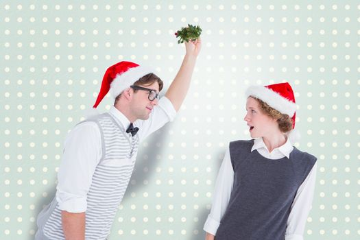 Composite image of geeky hipster holding mistletoe