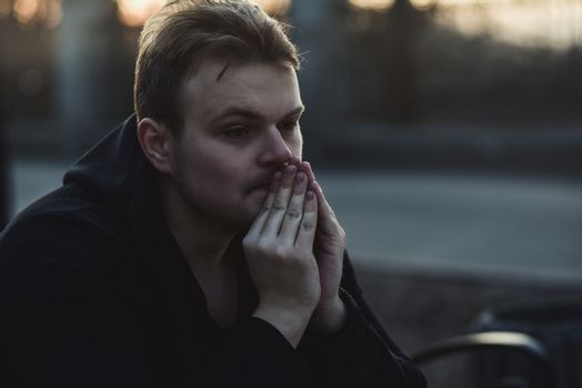 Portrait of a sad, depressed man sitting alone at street