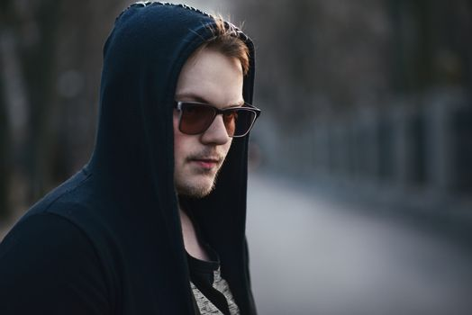 Portrait of fashion man in a black sweater with a hood and sunglasses