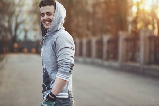 Sporty young man working out at early morning with background sunrise