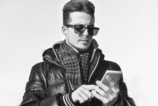 A Guy in a warm jacket with a smartphone in his hands, a sunny day.