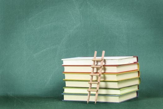 pencil ladder on stack of books against green chalkboard, education concept or background