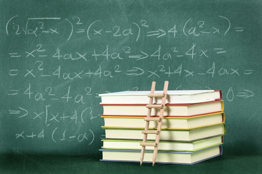 pencil ladder on stack of books against green chalkboard with equation