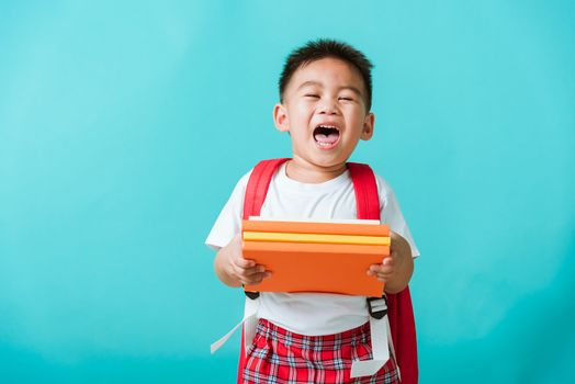 Back to school. Portrait Asian happy funny cute little child boy smiling and laugh holding books, studio shot isolated blue background. Kid from preschool kindergarten with school bag education