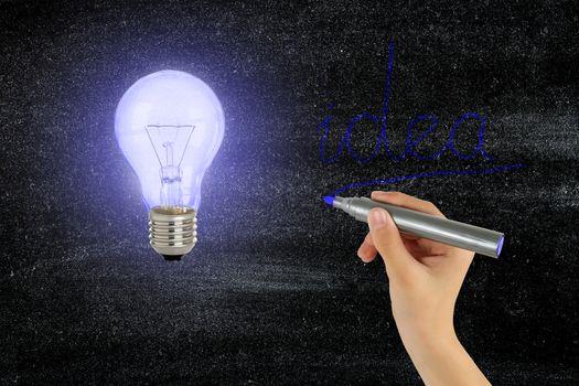 light bulb and hand writing idea on black board, idea concept