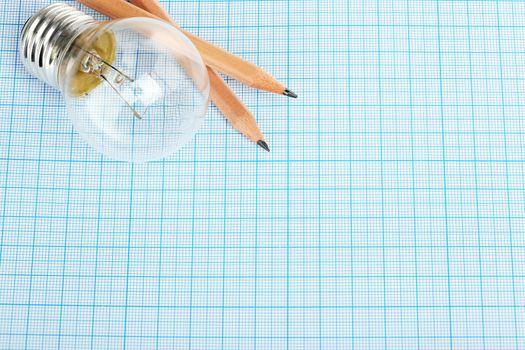 light bulb and pencils on millimeter paper, idea concept