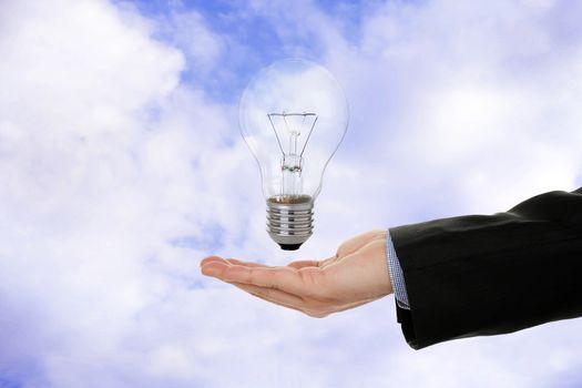 businessman's hand with light bulb against sky background, idea concept