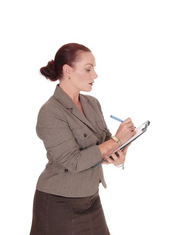 A serious looking business woman writing on her clipboard with a   blue pen, isolated for white background