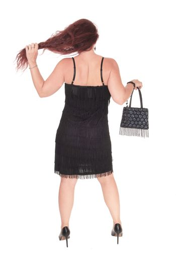 A beautiful woman standing in a black dress from the back with her long red hair, isolated for white background
