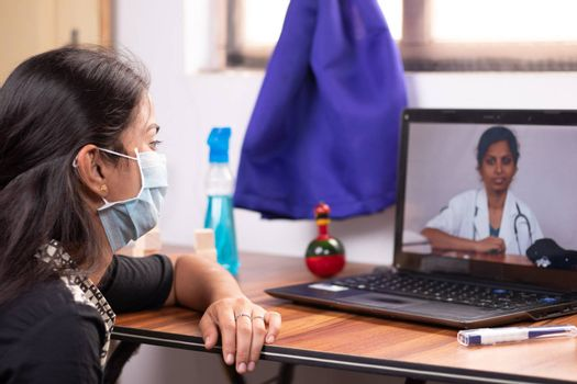 Concept of Online Chat, telehealth, or tele counseling with Nurse or Doctor on Screen during coronavirus or covid-19 pandemic - Girl in medical mask listening to doctor on laptop at home.