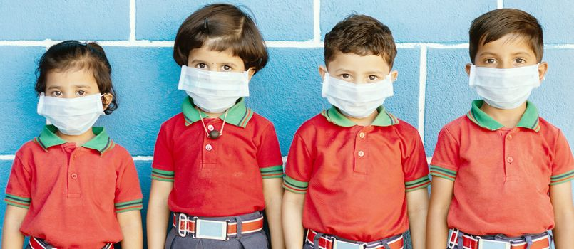 School preteen kids with protection face mask against new coronavirus, covid -19, nCov 2019 or sars cov 2 virus at school - children wore medical mask due to coronavirus outbreak