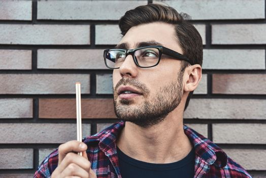 Portrait of handsome man in glasses and shirt isolated on brown brick wall.