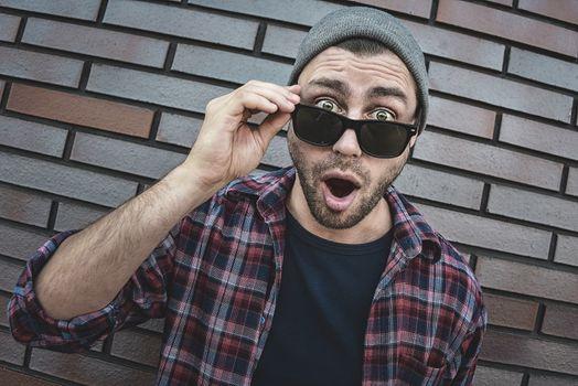 Shocked caucasian man in sunglasses standing at brick background.