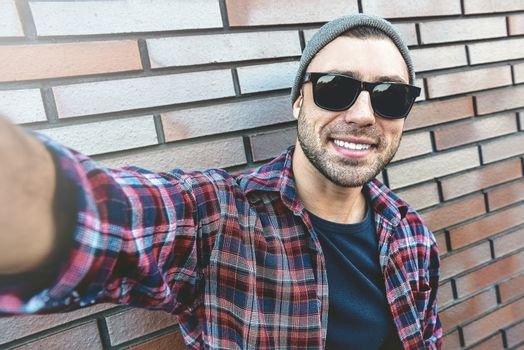 Portrait of stylish handsome young man with bristle standing outdoors and leaning on brick wall. Man wearing sunglasses and hat. Man making selfie.