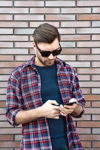 Front view of handsome young man in smart casual wear hold a mobile phone while standing at the brick wall background.